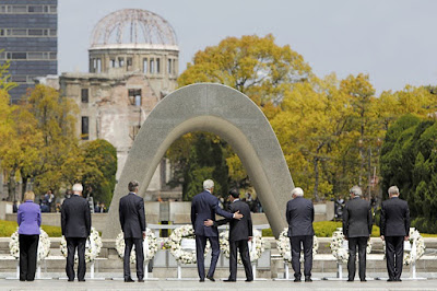 U.S. Secretary of State John Kerry puts his arm around Japan's Foreign Minister Fumio Kishida after they and fellow G7 foreign ministers laid wreaths at the cenotaph at Hiroshima Peace Memorial Park and Museum in Hiroshima, Japan